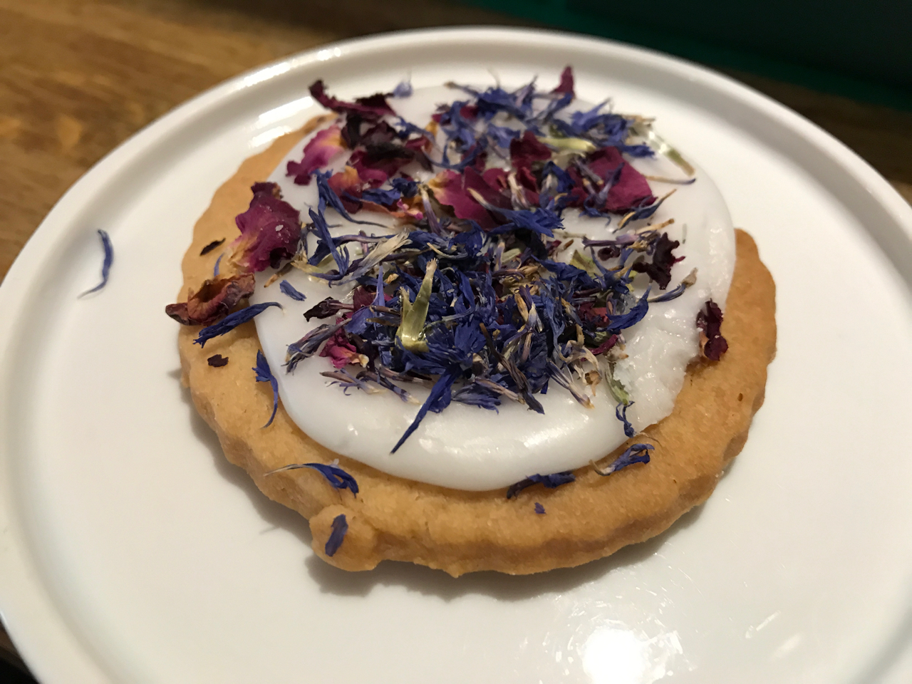 Sablés Aux Fleurs - A stunning shortbread cookie with white icing and purple and pink dried flowers at Peonies Café and Flower Shop in Paris, France.