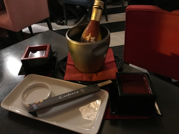 A bottle of sake, glasses and chopsticks sit on the table at Confraria Sushi, a Japanese restaurant in Cascais, Portugal. Photo Courtesy of FoodWaterShoes