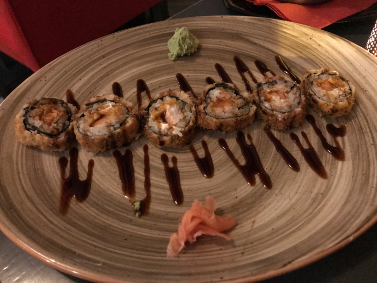 The shake cheese hot roll is deep fried and stuffed (frito recheado) with salmon (salmão). It's also made with mozzarella, tabasco and topped with chives (cebolinho). The roll is on the table at Confraria Sushi, a Japanese restaurant in Cascais, Portugal. Photo Courtesy of FoodWaterShoes