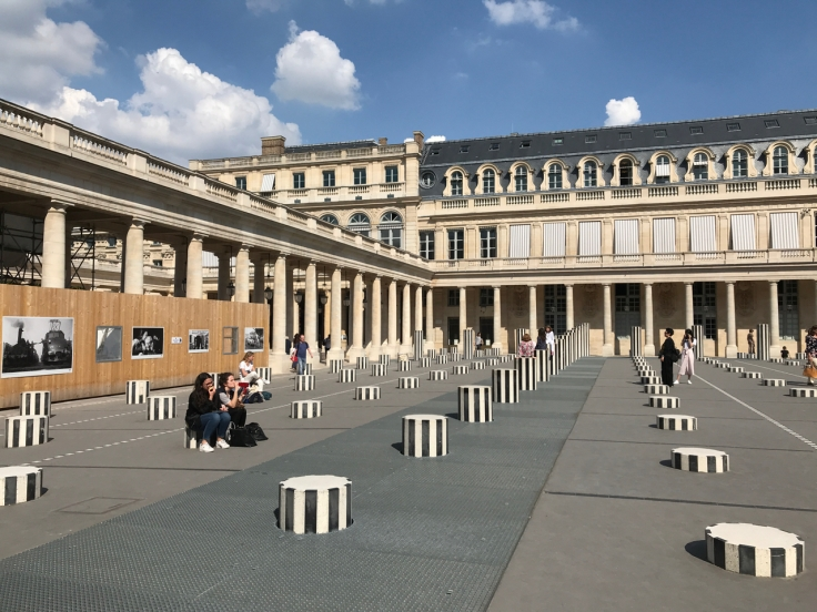 Black and white striped painted columns decorate the inner courtyard of the 17th Century Le Palais Royal (Royal Palace). The art installation is called the Colonnes de Buren (also known as Les Deux Plateaux) in Paris, France. Photo Courtesy of FoodWaterShoes