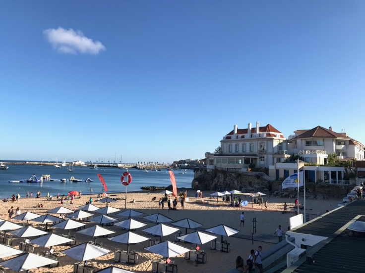Umbrellas and chairs are set up near the ocean alongside one of the beautiful beaches in Cascais, Portugal. Photo Courtesy of FoodWaterShoes