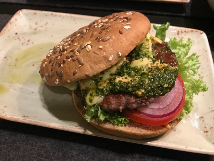 A träumer brie and pesto burger on a wheat bun filled with tomato, lettuce and red onions at Hans im Glück burger grill and restaurant in Stuttgart, Germany. Photo Courtesy of FoodWaterShoes