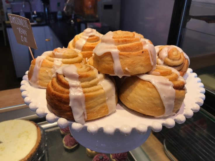 A cake stand holds a bunch of freshly made vegan cinnamon rolls (zimtschnecke) at Katjes Café Grün-Ohr coffee shop in Berlin, Germany. Photo Courtesy of FoodWaterShoes