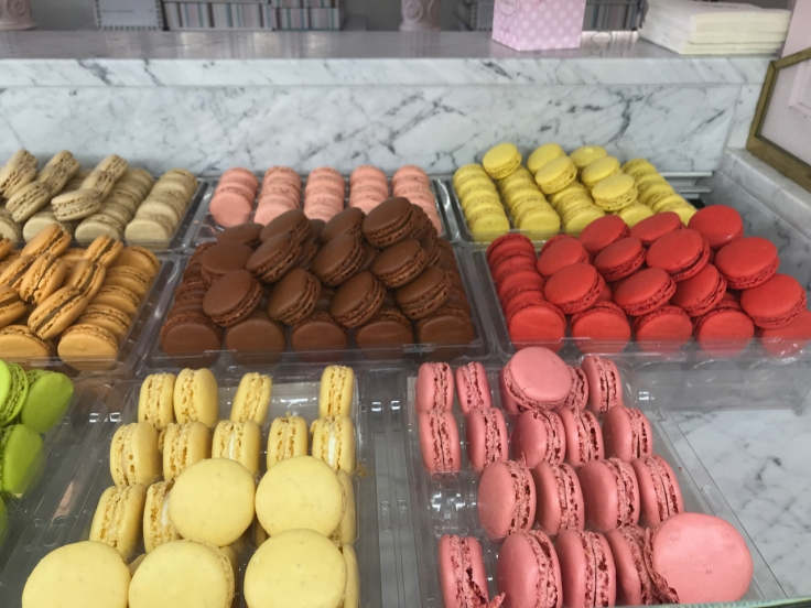 Brown, pink, red, yellow and green macarons on display at Cafeé Pouchkine in Paris, France. Photo Courtesy of FoodWaterShoes