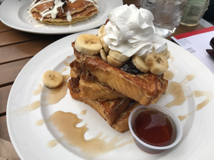A plate is piled high with PBB&J Texas style French toast topped with sliced bananas, whipped cream and powdered sugar at Mo's Breakfast + Burger Joint in Campbell, California. Photo Courtesy of FoodWaterShoes