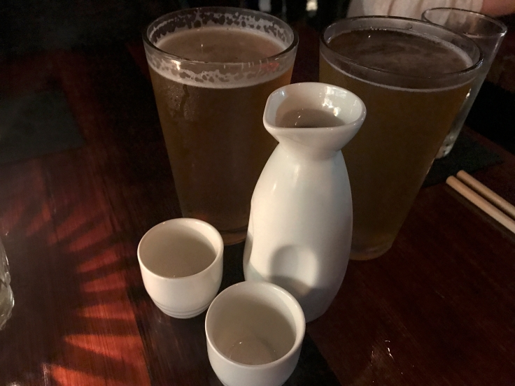 A photo of two pints of Hitachino white ale, a Belgium style white beer from Japan, sitting beside a carafe of house sake at Shōjō, a local Asian restaurant in Boston, Massachusetts' downtown Chinatown. Photo Courtesy of FoodWaterShoes
