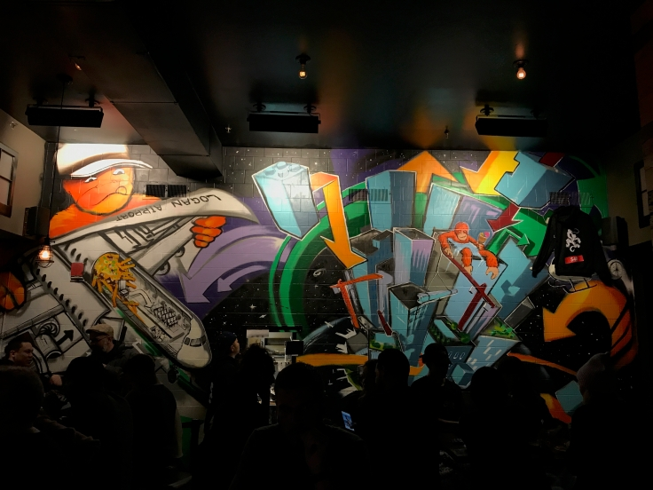 A photo of super cool hip graffiti mural featuring Logan Airport and an orange monkey character on the inside wall at Shōjō, a local Asian restaurant in Boston, Massachusetts' downtown Chinatown. Photo Courtesy of FoodWaterShoes