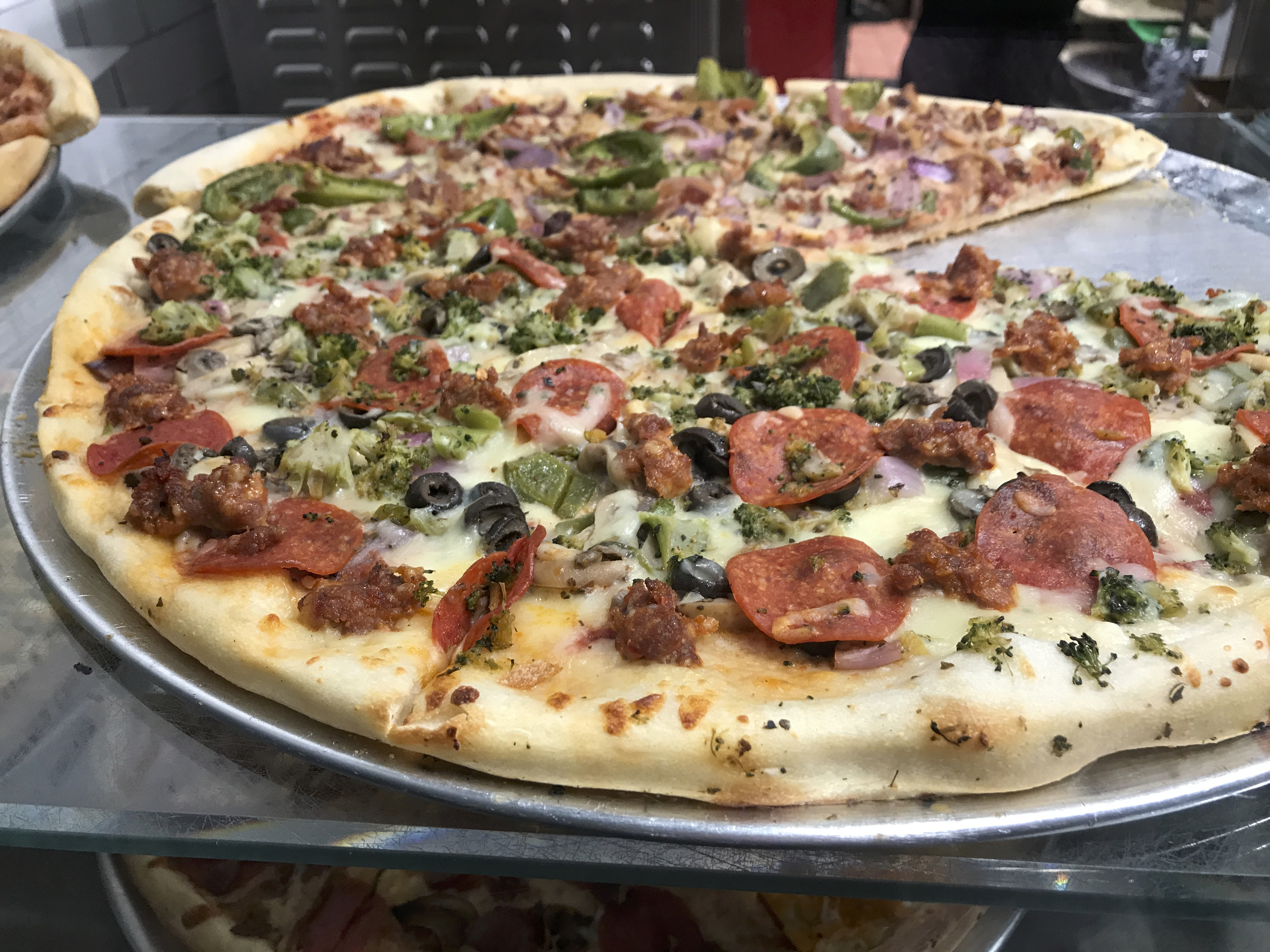 Put Your Money Where Your Mouth is - A photo of pizza with black olives, broccoli, onions, pepperoni and sausage. Slices at 2 Bros. Pizza in New York City, New York cost between $1.00 and $4.00. Photo Courtesy of FoodWaterShoes