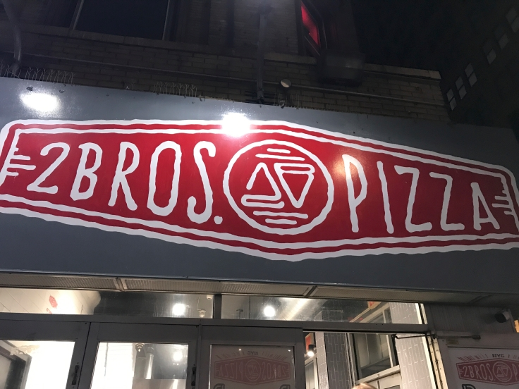 An exterior street view photo of the outside front of 2 Bros. Pizza in New York City, New York. Photo Courtesy of FoodWaterShoes.