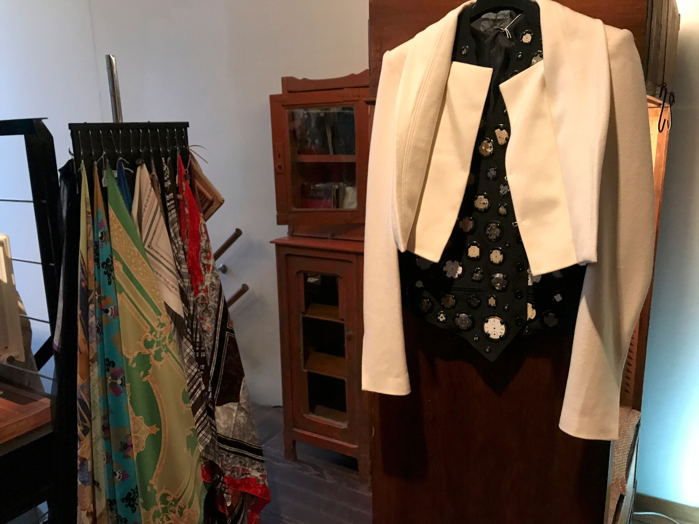 A photo of vintage Hermès scarves and a hip black clock watch vest styled with a white jacket at secondhand fashion boutique Isabelle Bajart in Brussels (Bruxelles), Belgium. Photo Courtesy of FoodWaterShoes