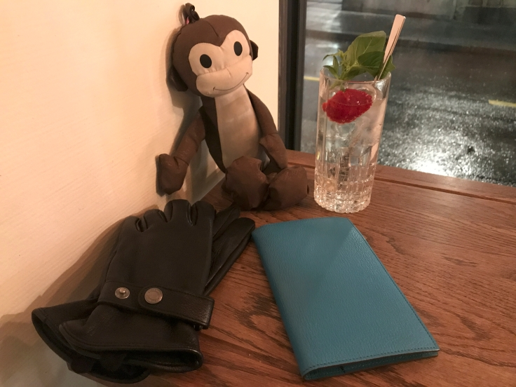 A photo of Aigle black leather gloves with snaps, a blue Hermès notebook, a Salvador Bachiller monkey umbrella and a gin and tonic. Photo Courtesy of FoodWaterShoes