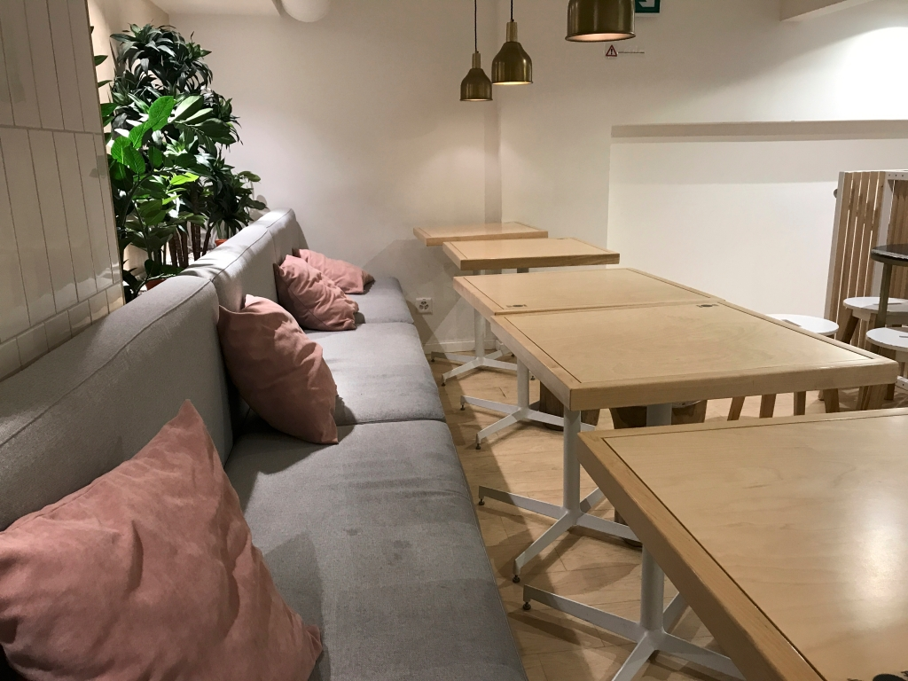 A photo of the grey benches with pink pillows at Pancs, a fast food restaurant that serves chicken pancake burgers in Lausanne, Switzerland. Photo Courtesy of Food WaterShoes