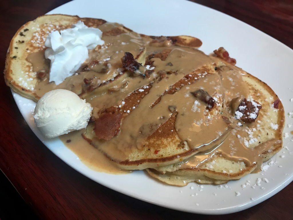A photo of the Elvis B-side at Modern Malt in Syracuse, New York. The dish consists of three bacon and banana stuffed pancakes topped with peanut butter drizzle. Photo Courtesy of FoodWaterShoes