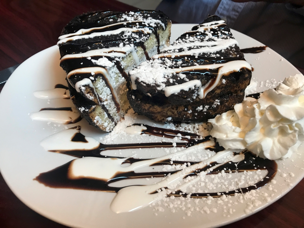 A photo of Oreo stuffed French toast at local hot spot Modern Malt in Syracuse, New York. The toast is filled with Oreo buttercream and drizzled with chocolate and marshmallow sauce. Modern Malt is an upstate New York CNY based diner that serves breakfast, lunch and dinner. Photo Courtesy of FoodWaterShoes