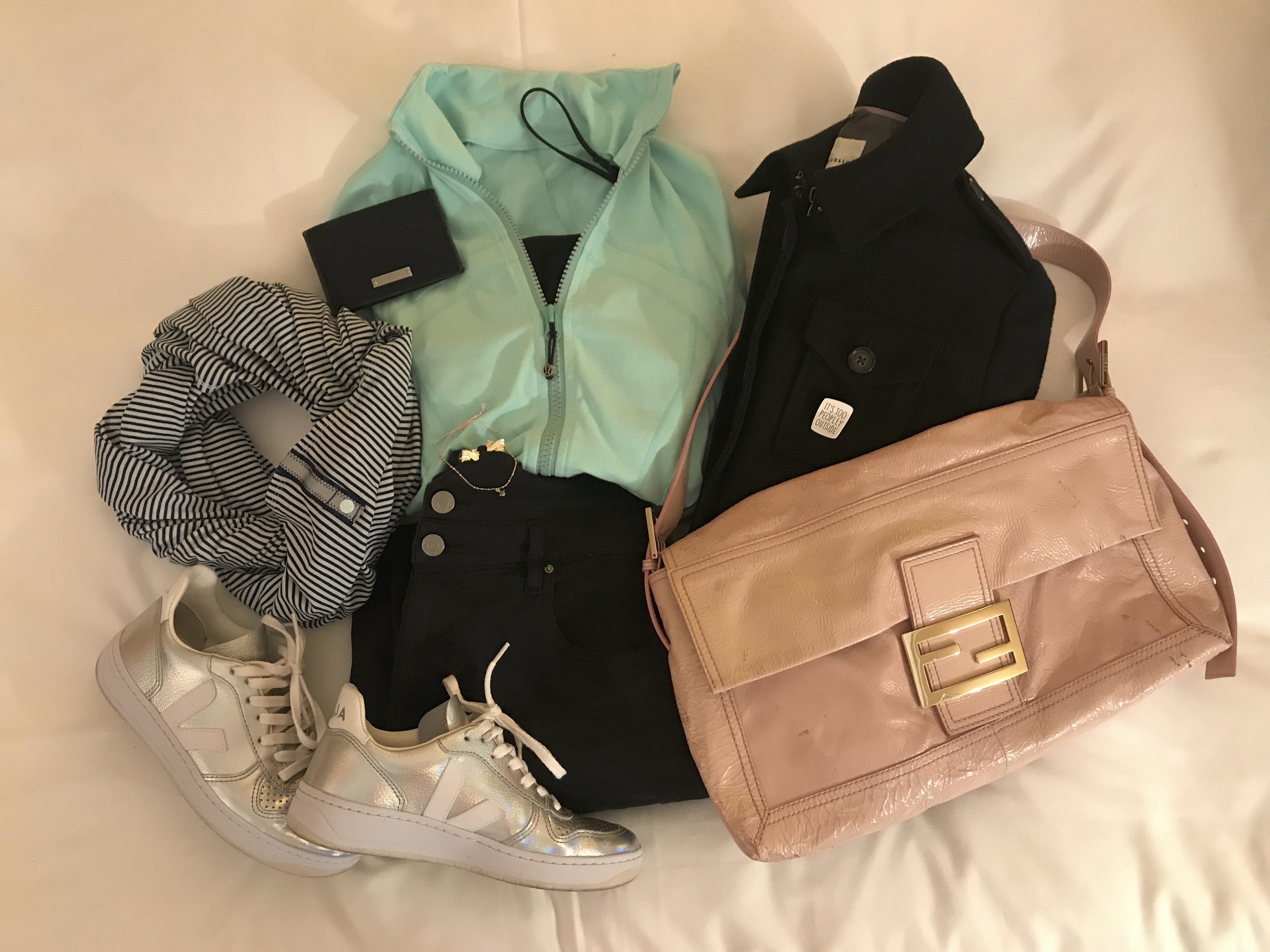 A photo of a Lululemon vinyasa reversible Rulu striped scarf (in hyper stripe sea mist and hero blue), Veja V-10 unicorn sneakers, a large pink Fendi baguette bag, black Isabel Marant high waist denim jeans, a plain black tank top, a black Gucci wallet and a mint forme jacket from Lululemon.