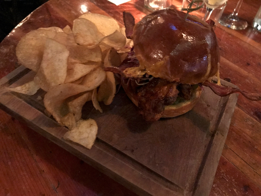 A photo of the fried chicken sandwich at local hot spot Mindy's Hot Chocolate Chicago in Chicago, Illinois. The dish is made with a buttermilk fried chicken thigh, a brioche bun, cheddar, hot sauce maple syrup and served with potato chips as well as house made pickles. The Windy City based dessert restaurant serves brunch, cocktails, drinks, lunch and dinner. Photo Courtesy of FoodWaterShoes