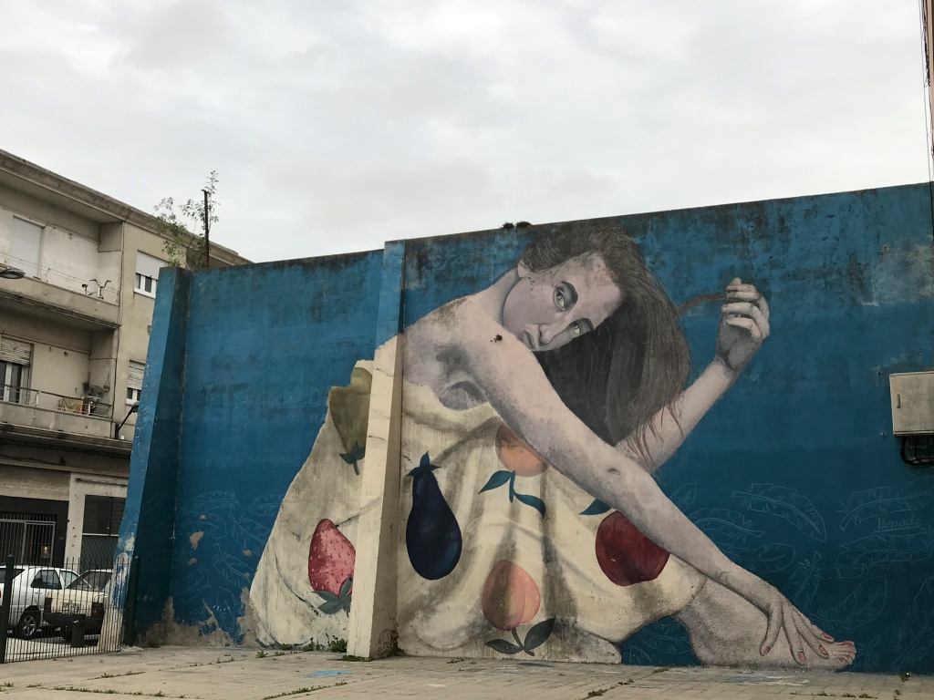 A photo of graffiti by Colectivo Licuado (which consists of street artists Camilo Núñez and Florencia Durán) in Montevideo, Uruguay. The wall mural features a woman (or a girl) in a dress covered with fruit and is one of the sights to see / things to do in Montevideo.