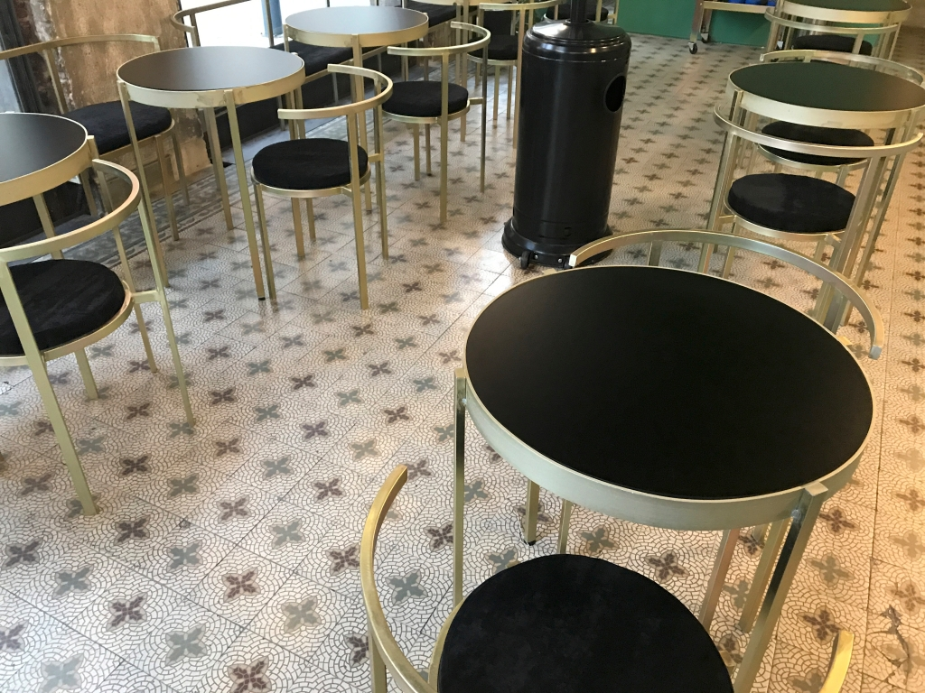 A photo of a pretty tiled floor topped with elegant gold chairs and tables at Nómade, a café in Montevideo, Uruguay. Photo Courtesy of FoodWaterShoes