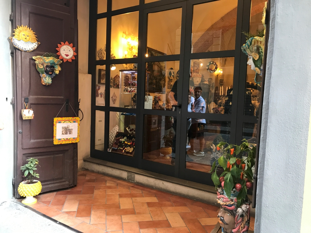 A photo of the front door to Sikuliana Art Atelier, a Sicilian ceramics and jewelry store in Florence, Italy. The photo is of the exterior / is an outside street view shot of the accessories boutique. Photo Courtesy of FoodWaterShoes