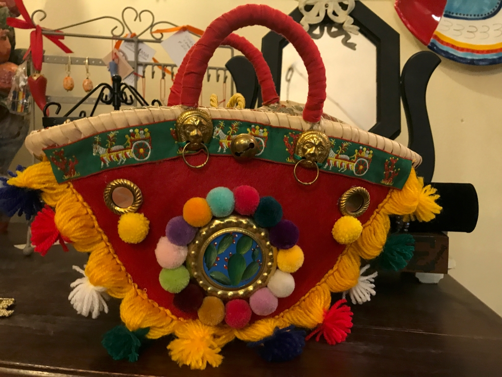 A photo of a handmade red basket bucket bag with colorful pompoms at Sikuliana Art Atelier in Florence, Italy. Photo Courtesy of FoodWaterShoes