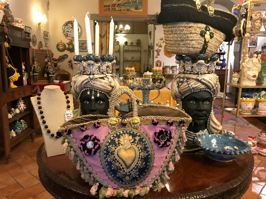 A photo of a pair of Teste di Moro, Sicilian head shaped vases, and a pink handbag at Sikuliana Art Atelier in Florence, Italy. Photo Courtesy of FoodWaterShoes
