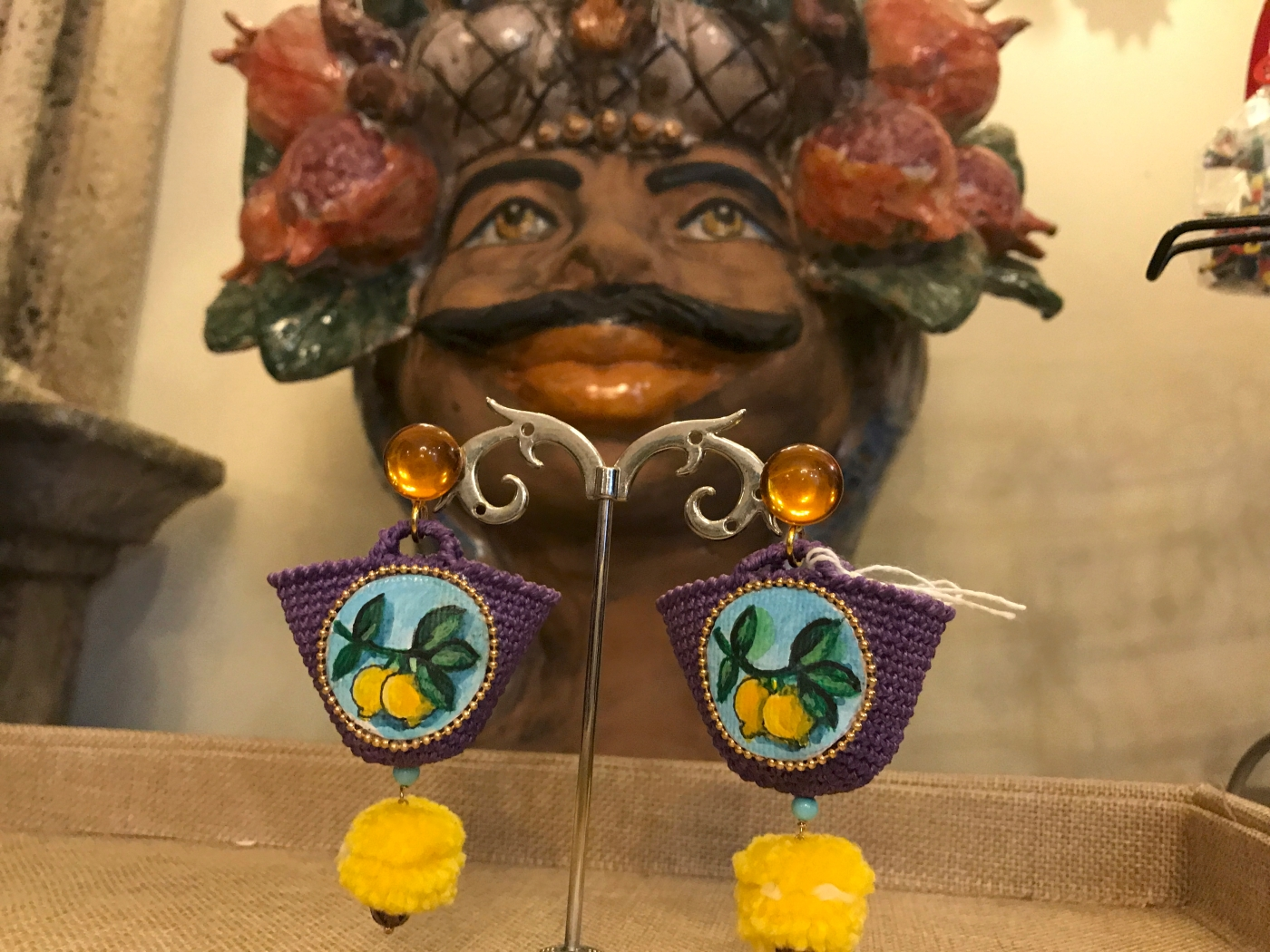 A photo of a Teste di Moro head shaped vase and handmade purple Sicilian basket earrings with yellow lemons and pompoms at Sikuliana Art Atelier in Florence, Italy. Photo Courtesy of FoodWaterShoes
