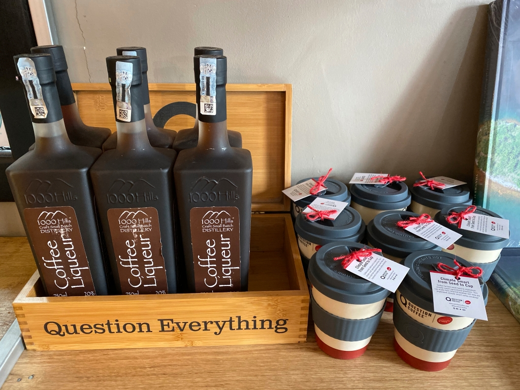 A photo of bottles of coffee liqueur from 1000 Hills Distillery and other souvenirs on a shelf at Question Coffee, a cute cafe in Kigali, Rwanda. Photo Courtesy of FoodWaterShoes