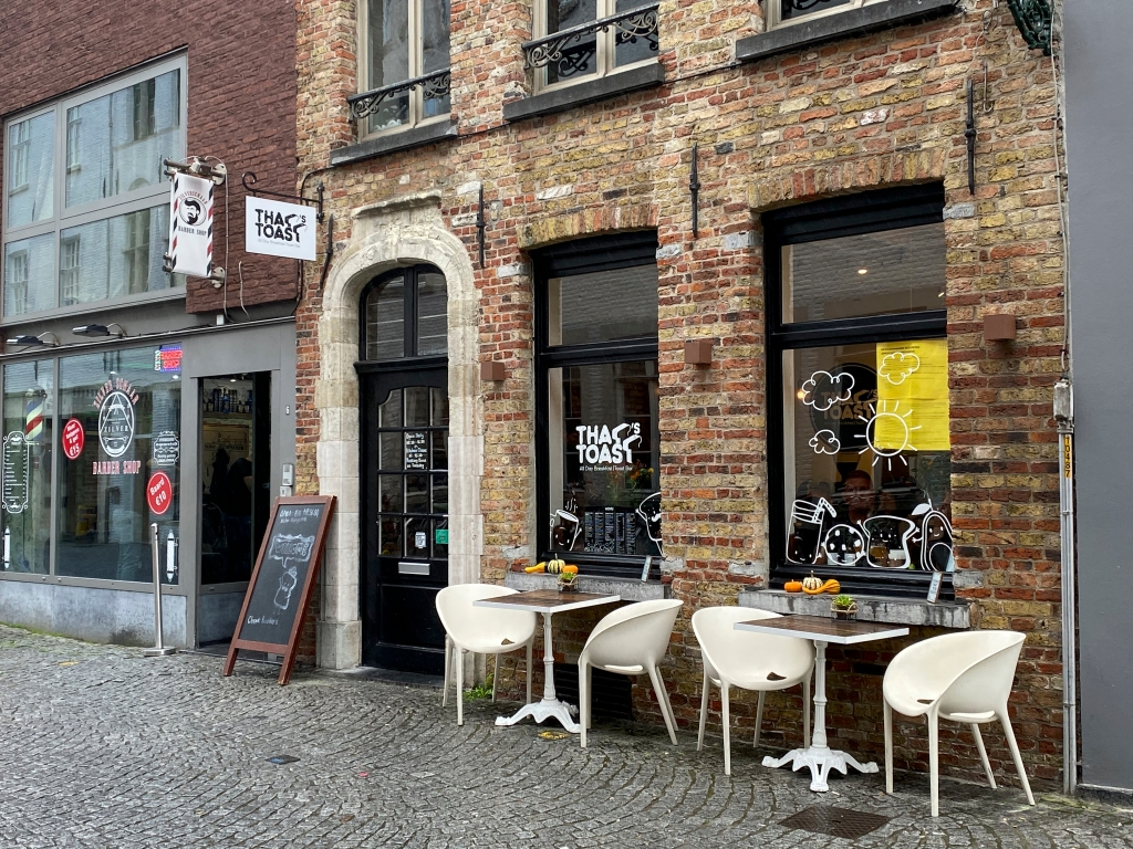 A photo of the patio outside exterior street view of That's Toast, a cute little café restaurant in Bruges, Belgium. Photo Courtesy of FoodWaterShoes