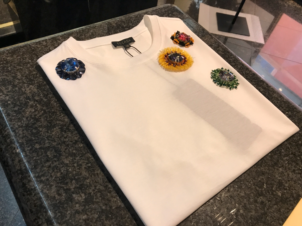 A photo of a white Escada t-shirt with rhinestones, beads and Swarovski flower details at Bottega Giuliana, a cute boutique in Verona, Italy.