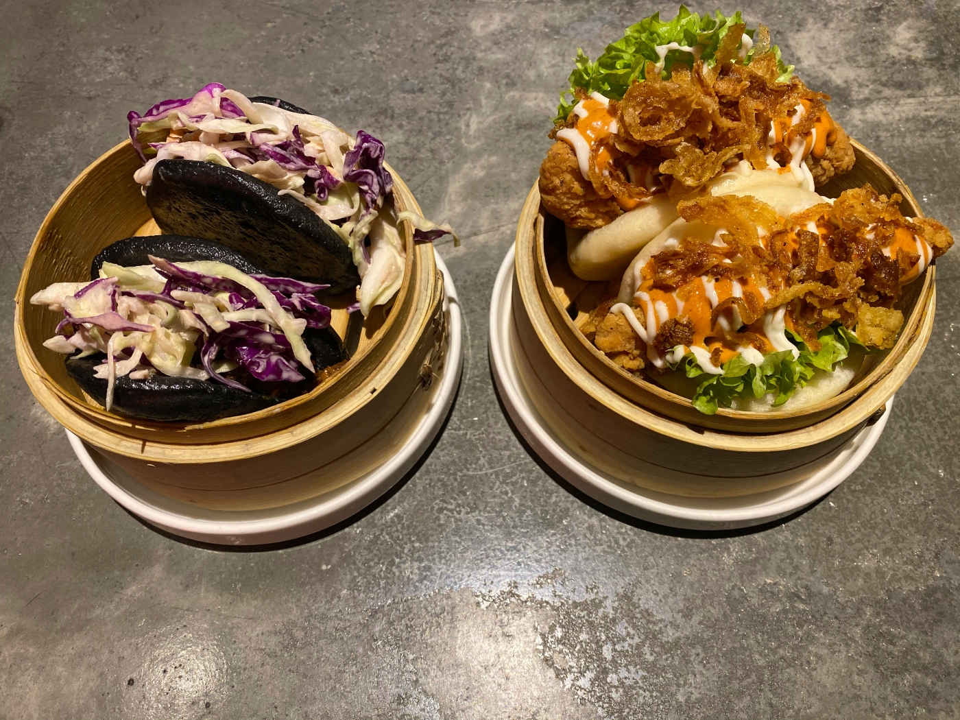 A photo of slow cooked beef brisket baos with smoky BBQ barbecue sauce in charcoal buns and chicken loca baos with crispy onions and chipotle sauce at Baozi باوزي a restaurant in Riyadh, Saudi Arabia. Photo Courtesy of FoodWaterShoes