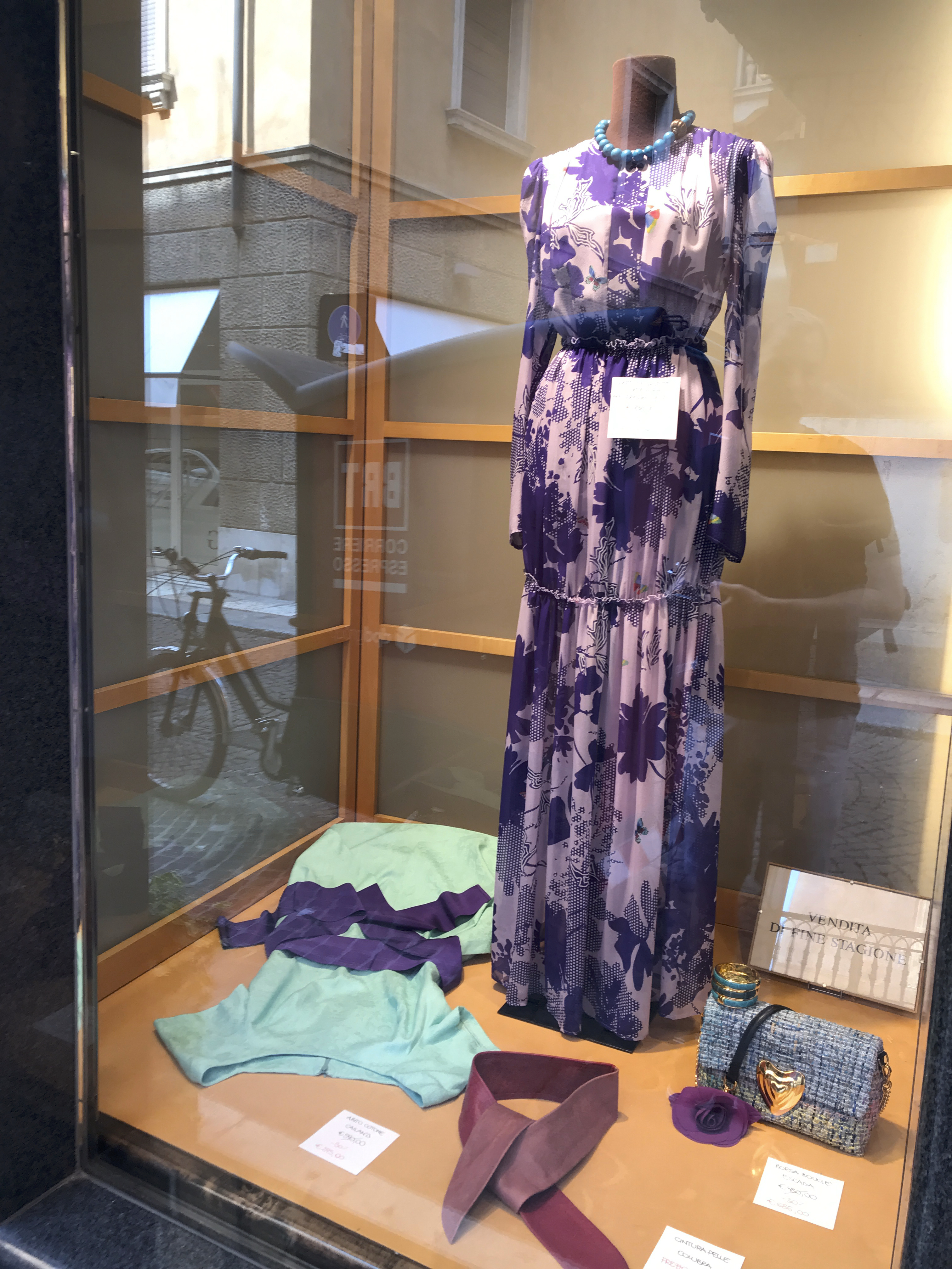A photo of a purple floral Escada gown in a window beside an Escada heart bag in rainbow tweed at Bottega Giuliana, a cute shop in Verona, Italy.
