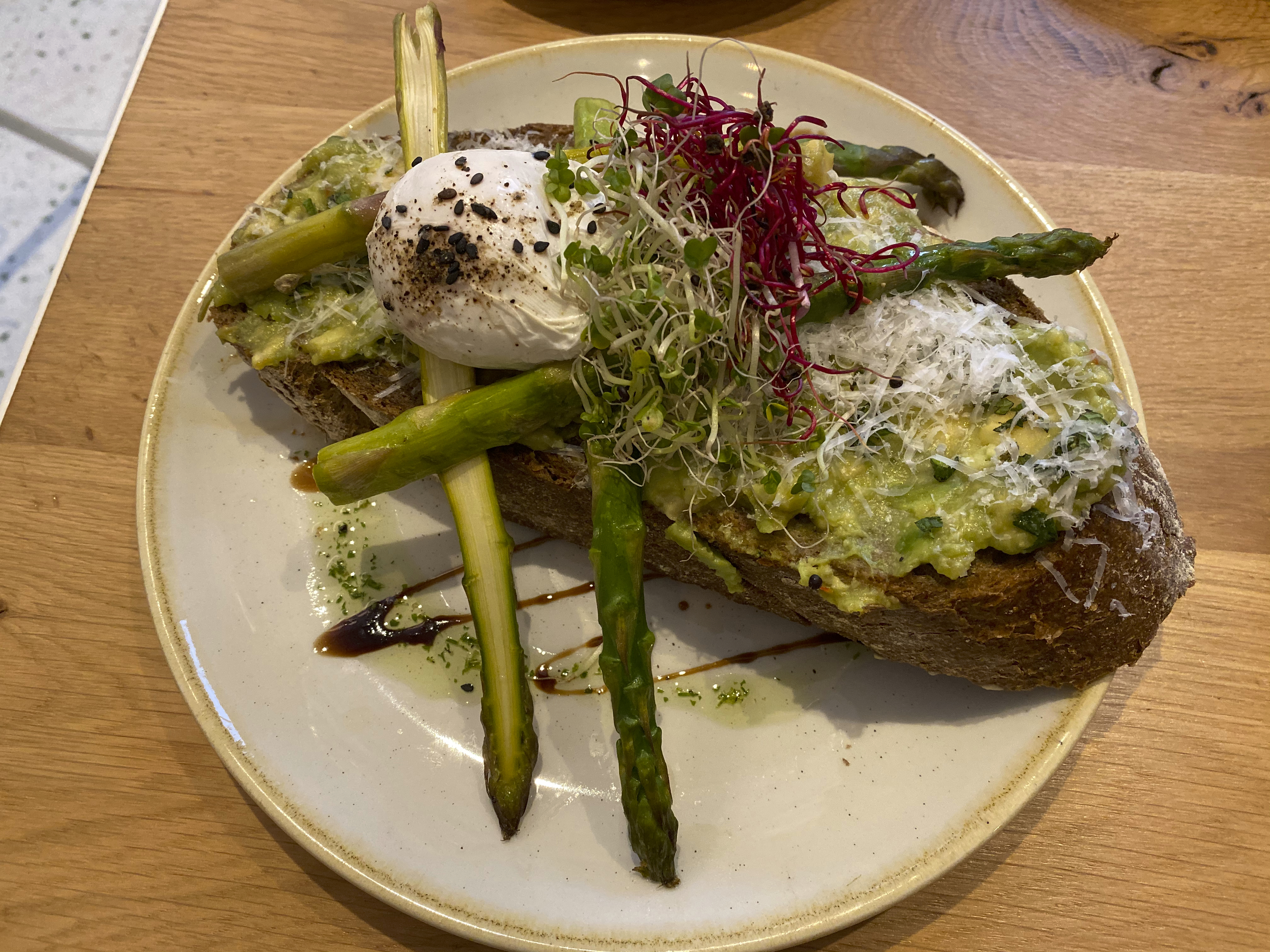 A photo of the classic (avocado salsa, green asparagus, Grana Padano cheese, mint, toast and a poached egg) at That's Toast, a cute little café restaurant in Bruges, Belgium. Photo Courtesy of FoodWaterShoes