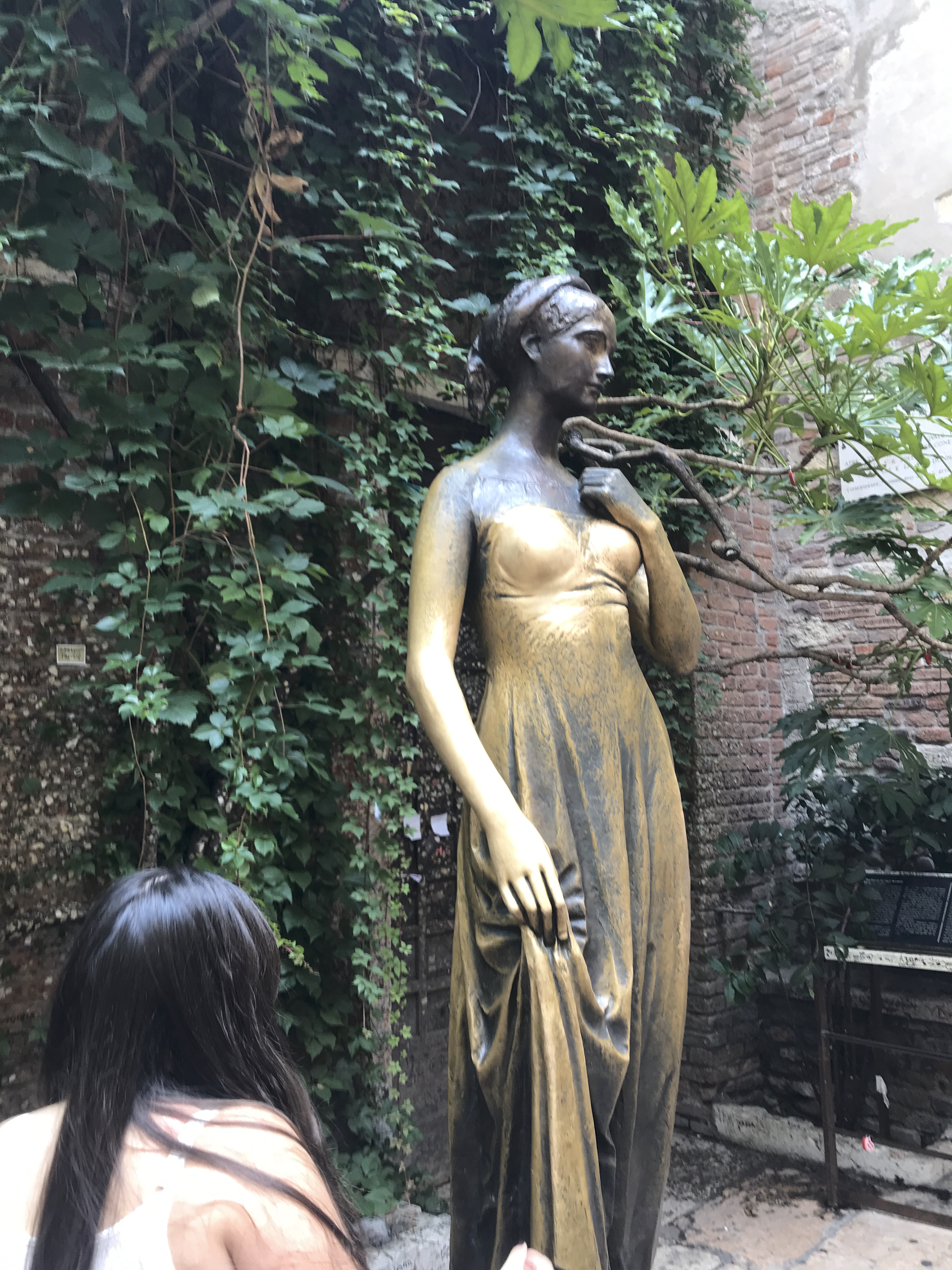 A photo of a tourist looking at the gold statue of Juliet in a courtyard in Verona, Italy. Photo Courtesy of FoodWaterShoes