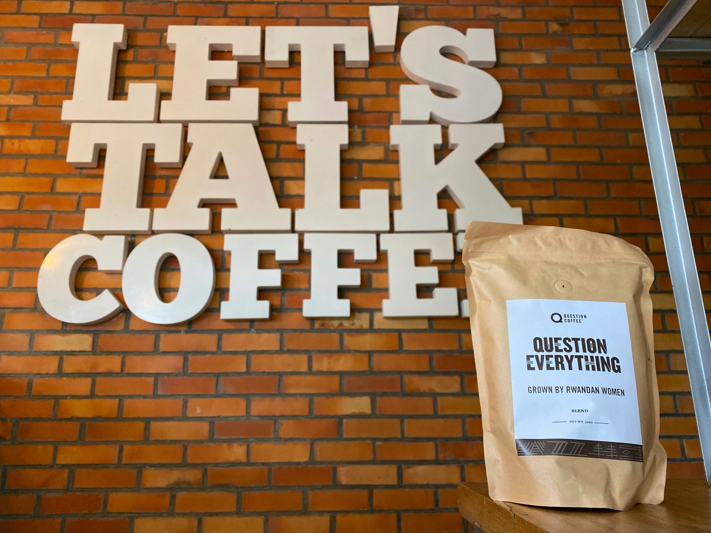 "A photo of a bag of beans and a sign that says, ""Let's Talk Coffee,"" inside Question Coffee, a cute café in Kigali, Rwanda. The bag of beans says, ""Question Everything Grown By Rwandan Women,"" Photo Courtesy of FoodWaterShoes"
