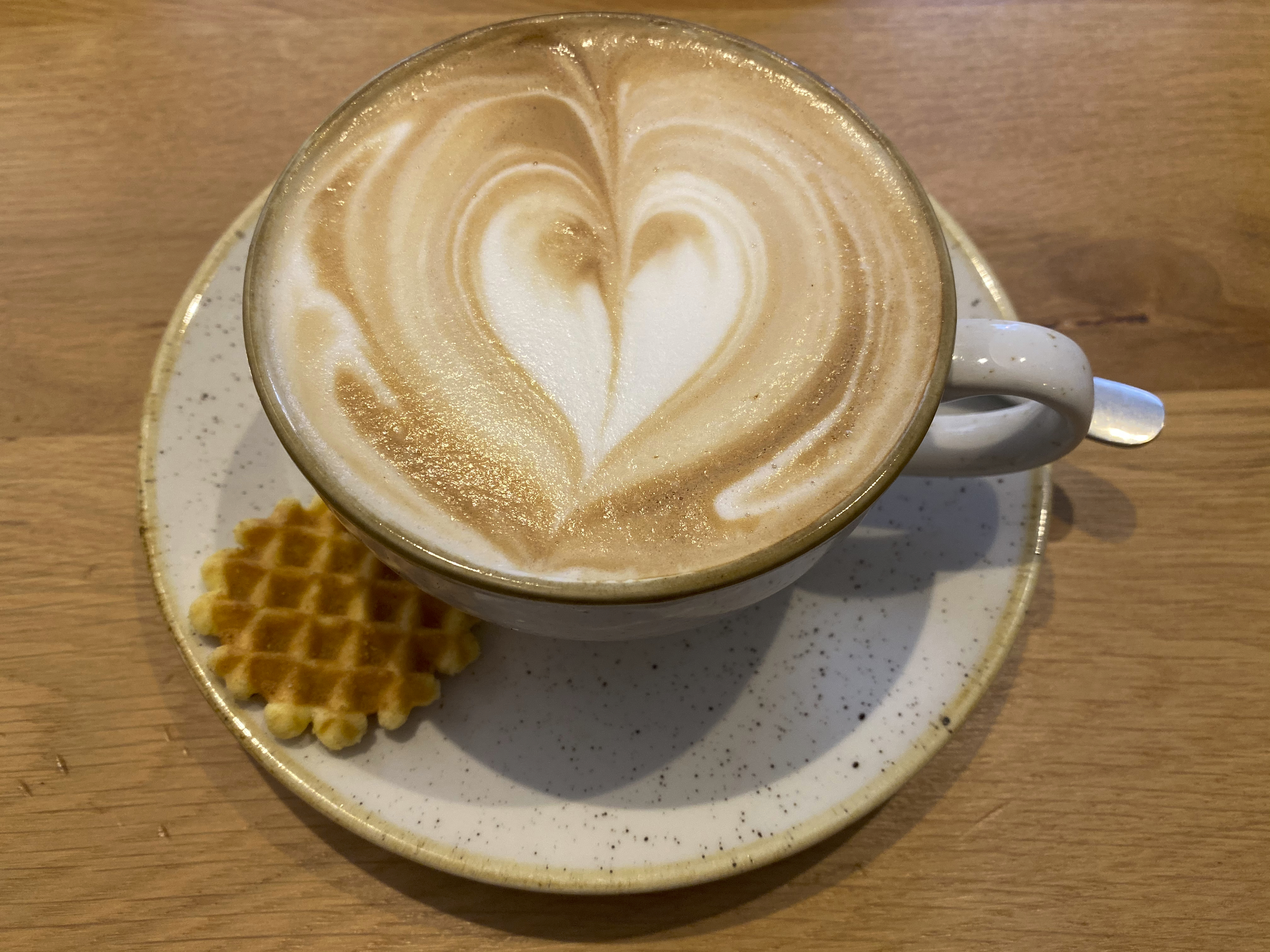 A photo of a cappuccino accompanied by a mini Belgian waffle cookie at That's Toast, a cute little breakfast and brunch restaurant café, in Bruges, Belgium. Photo Courtesy of FoodWaterShoes