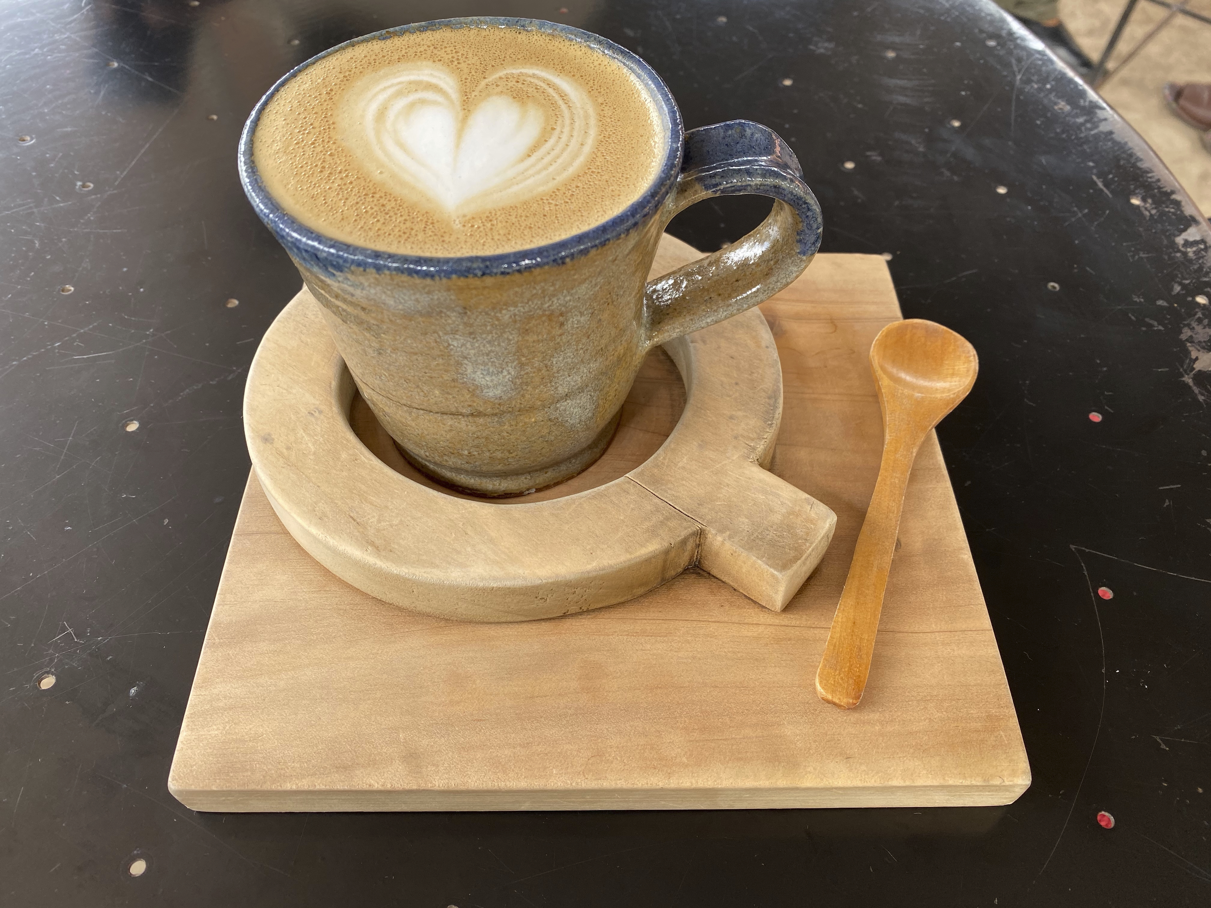 A photo of a cappuccino with beautiful coffee art at Question Coffee, a cute cafe in Kigali, Rwanda. The cup is nestled inside a wooden board shaped like the letter Q. Photo Courtesy of FoodWaterShoes