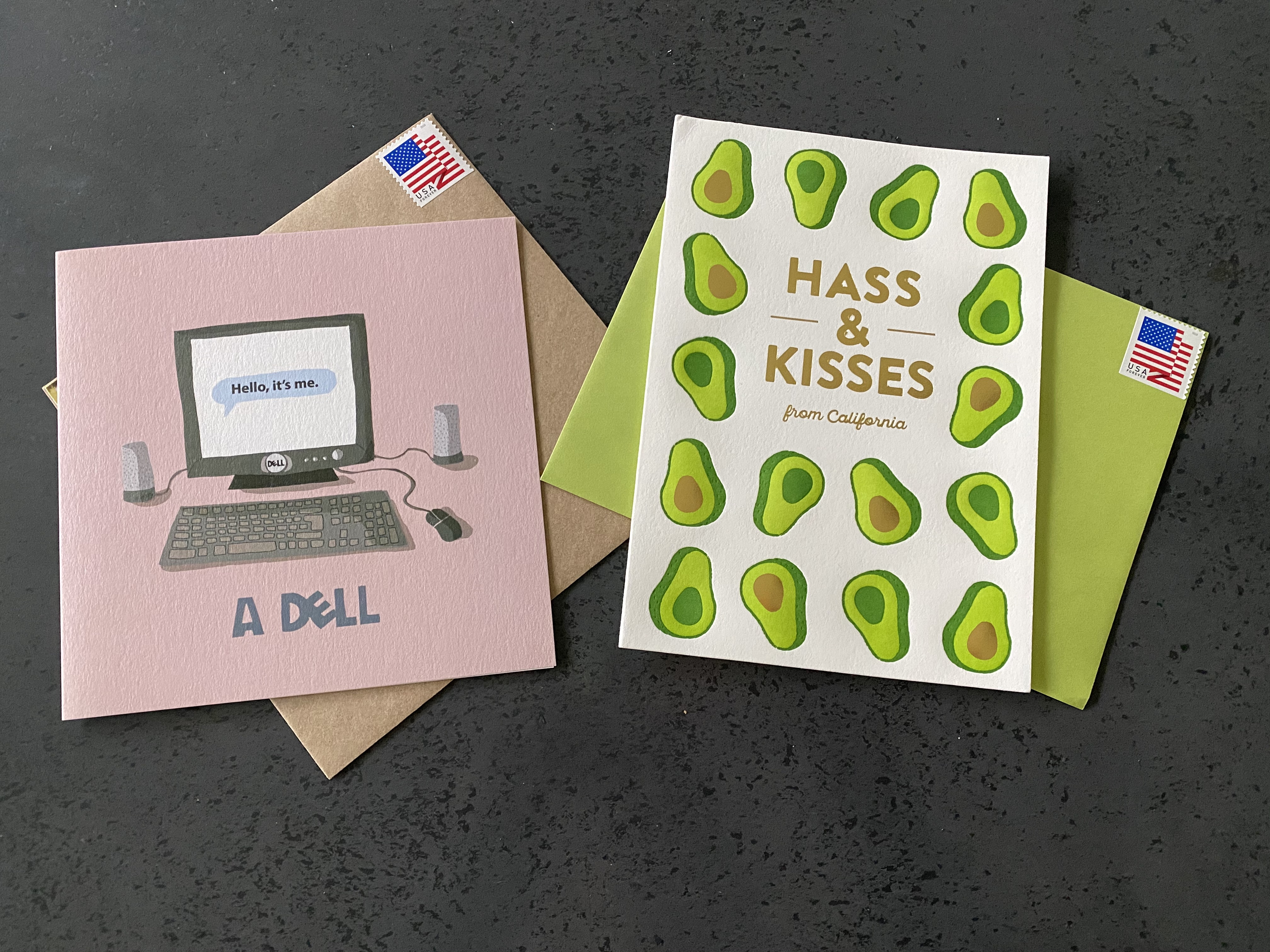 "A photo of two funny punny greeting cards. One designed by Ohh Deer says, ""Hello, It's me. A dell."" Another card by Elum Designs says, ""Hass & Kisses From California."" Photo Courtesy of FoodWaterShoes"