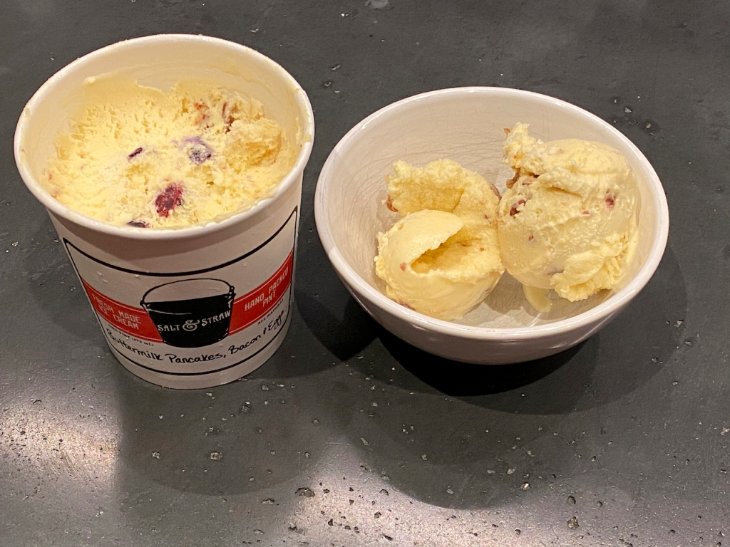 A photo of an ice cream pint and a bowl filled with an exotic flavor called buttermilk pancakes, bacon and eggs from Salt & Straw in California. Photo by FoodWaterShoes